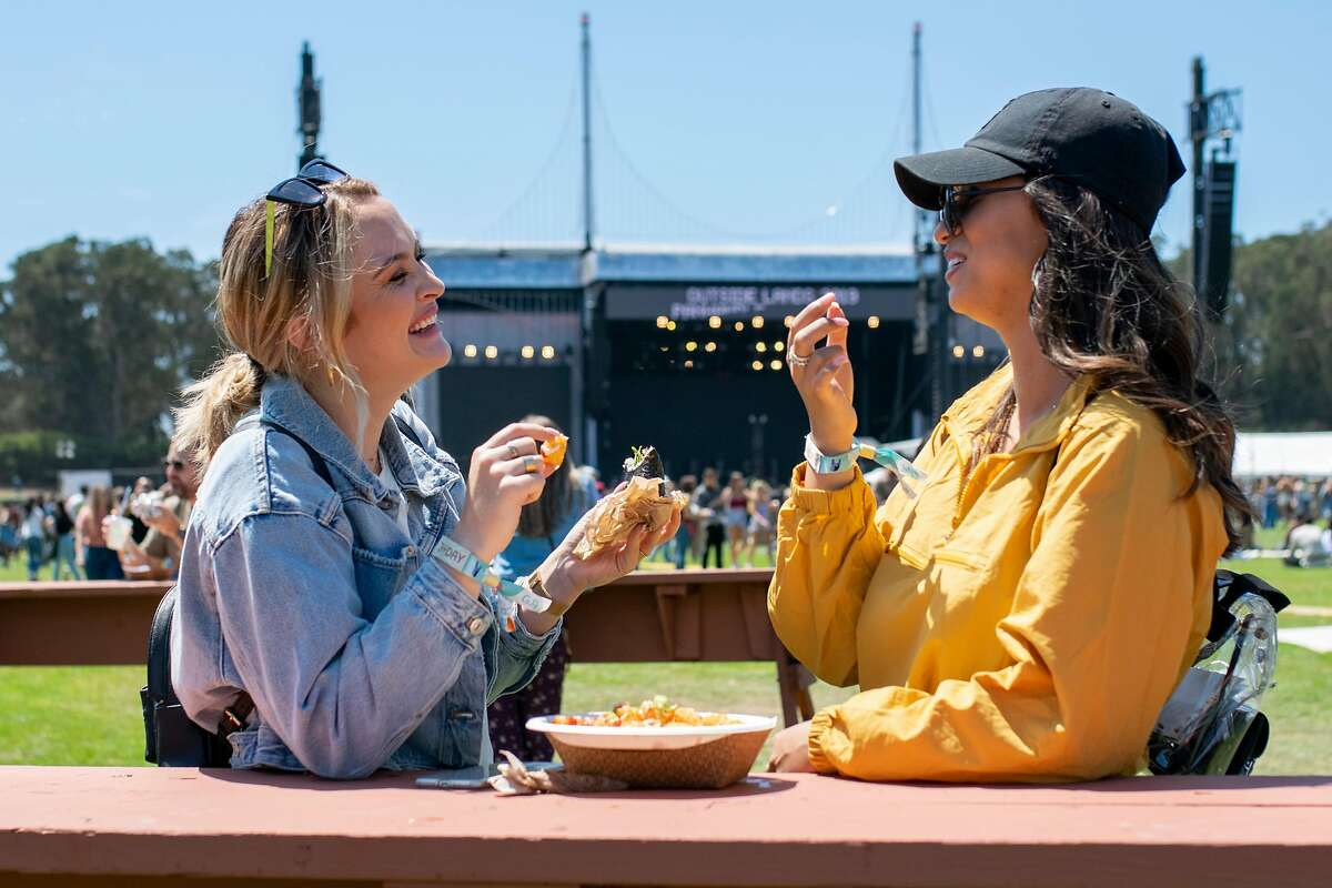 From left: Ann Reidy and Teryssa Pineda eat a sushirrito and tater tots at Outside Lands on Friday, Aug. 9, 2019, in San Francisco, Calif.