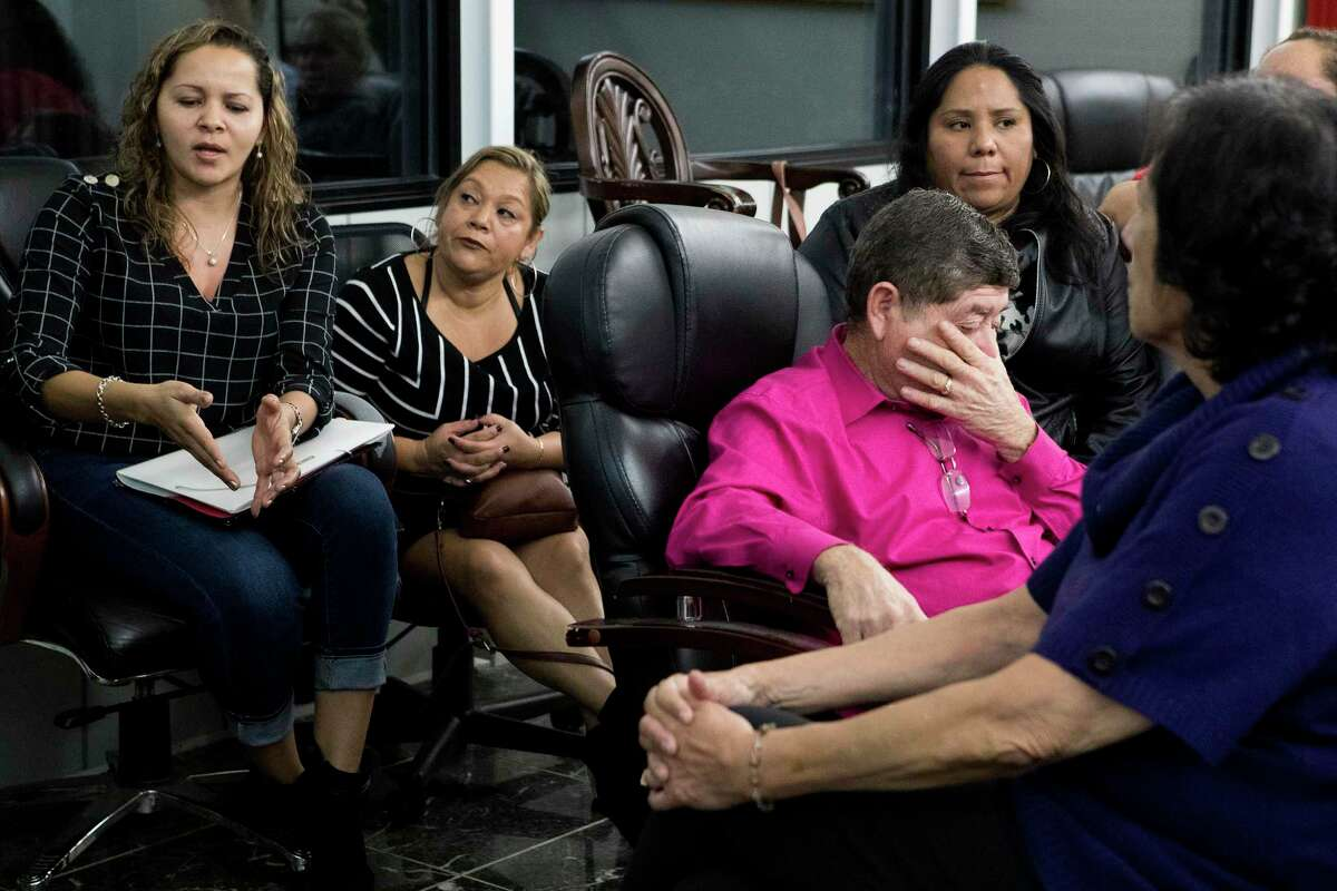 Karen Molina, far left, speaks during a meeting of those suing their condominium homeowners association.