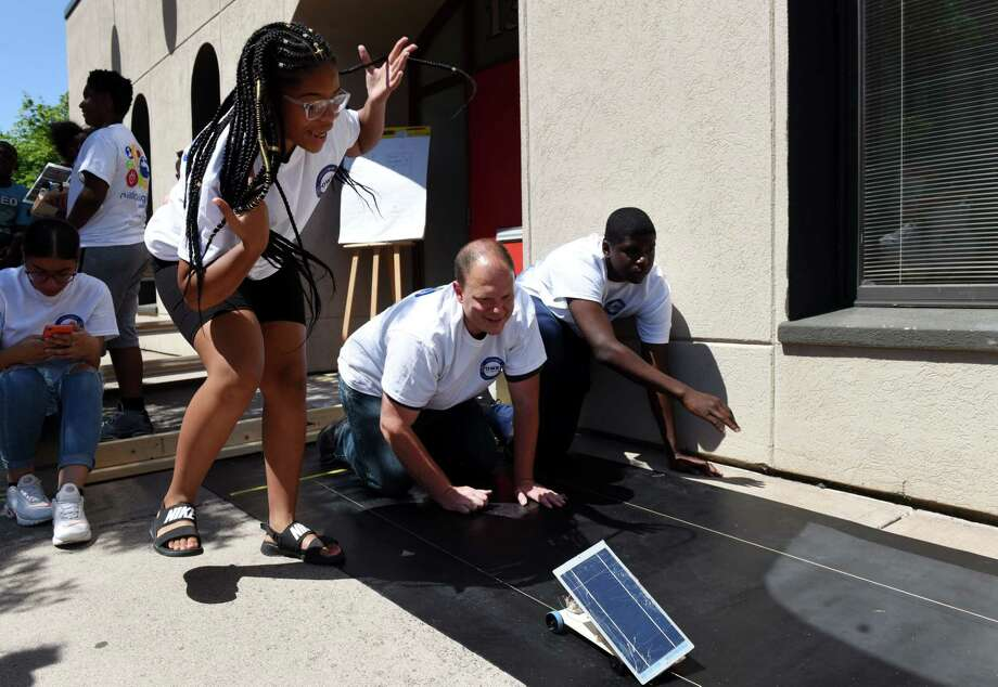 TisA½ Sanchez, left, urges on her solar powered car during a three-day trades camp put on by Nation Grid and the Social Enterprise and Training Center on Friday, Aug. 9, 2019, at the SEAT Center in Schenectady, N.Y. During the camp students ages 13 - 15 were given the opportunity to learn about various trades including: carpentry, plumbing, and electrical. (Will Waldron/Times Union) Photo: Will Waldron / 40047624A