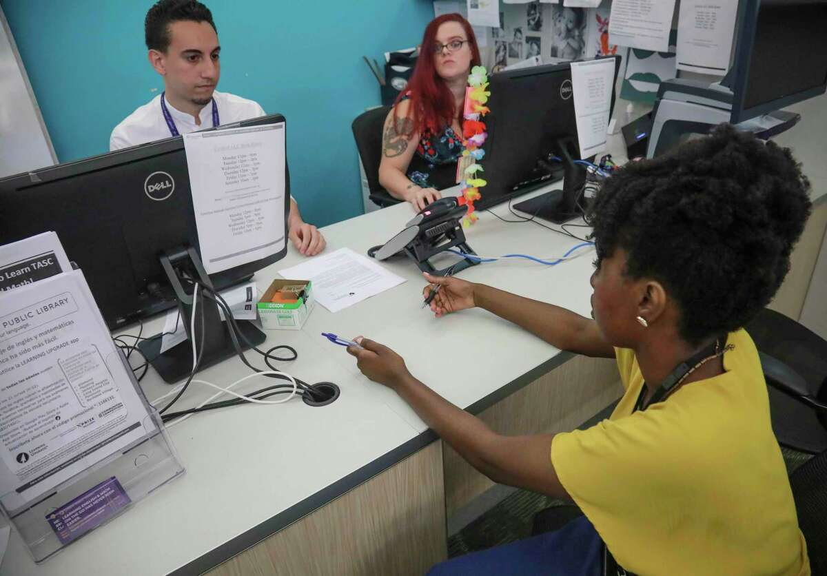 Shantel Johnson, right, a full time social worker at Queens Central Library, and Michael Montero, left, social work summer intern from NYU, meet at the library's coordinating desk for adult services, Monday July 29, 2019, in Queens borough of New York. Johnson oversees a team of case managers and help librarians connect visitors to social services.