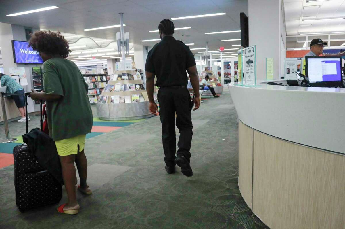 Security guard Reginald Rudolph, center, makes his rounds at Queens Central Library, Monday July 29, 2019, in Queens borough of New York. Security personnel often become frontline contact between patrons and library social workers.