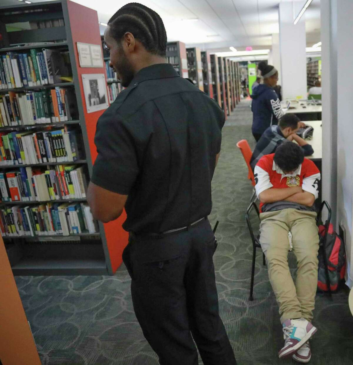 Security guard Reginald Rudolph, left, makes his rounds at Queens Central Library, Monday July 29, 2019, in Queens borough of New York. Security personnel often become frontline contact between patrons and library social workers.