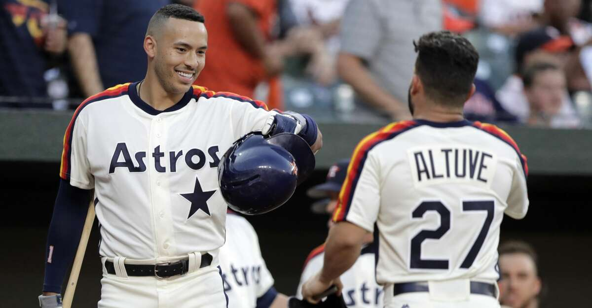 Houston Astros' Jose Altuve, right, is greeted in the dugout by Carlos Correa after scoring on a hit by Alex Bregman during the first inning of a baseball game against the Baltimore Orioles, Friday, Aug. 9, 2019, in Baltimore. (AP Photo/Julio Cortez)