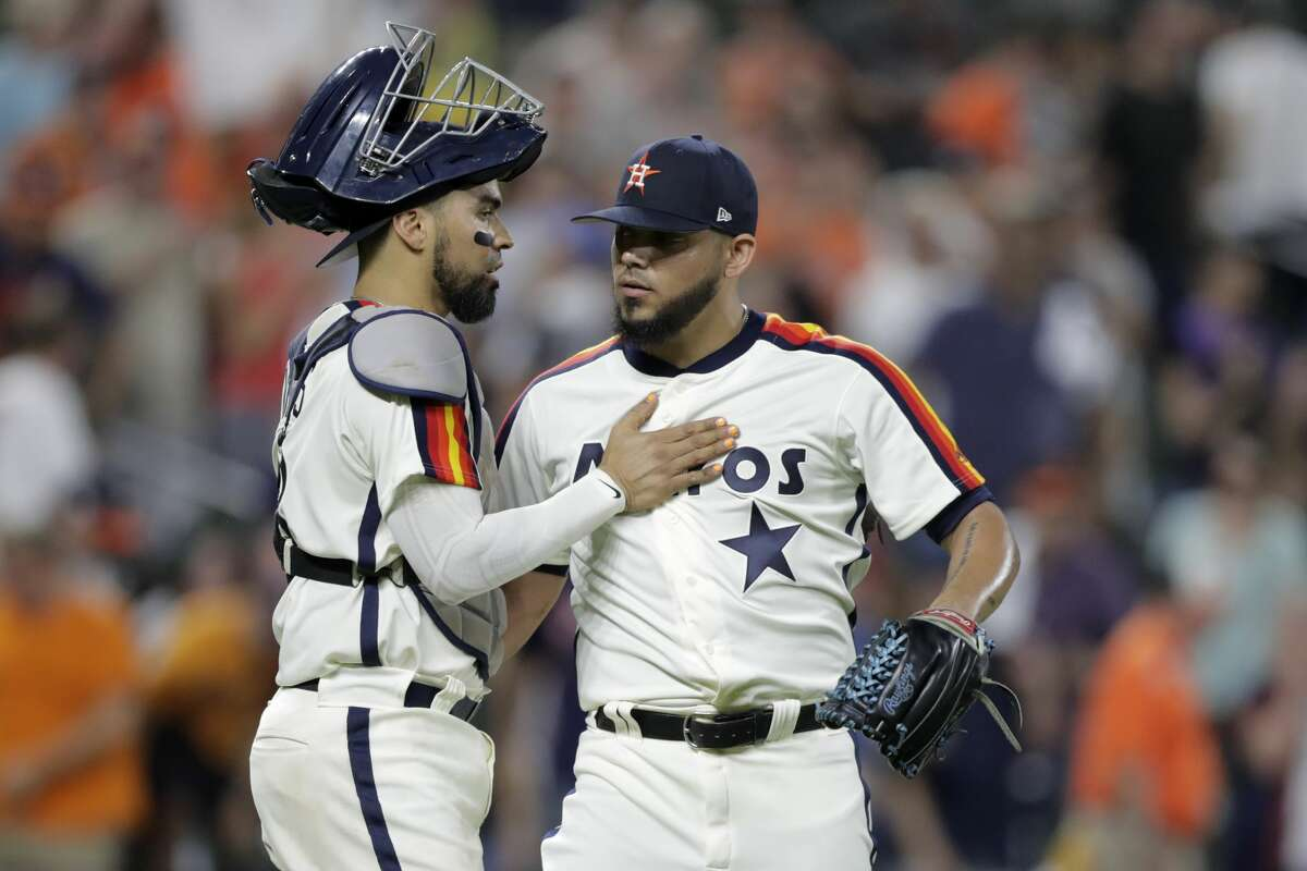 Houston Astros catcher Robinson Chirinos, left, celebrates with relief pitcher Roberto Osuna after defeating the Baltimore Orioles in a baseball game, Friday, Aug. 9, 2019, in Baltimore. (AP Photo/Julio Cortez)