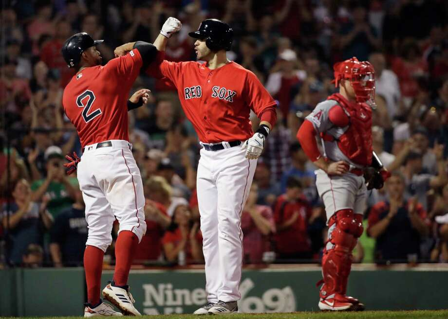 Boston Red Sox's J.D. Martinez, right, celebrates his two-run home run with Xander Bogaerts, next to Los Angeles Angels catcher Max Stassi during the fourth inning of a baseball game at Fenway Park, Friday, Aug. 9, 2019, in Boston. (AP Photo/Elise Amendola) Photo: Elise Amendola / Copyright 2019 The Associated Press. All rights reserved