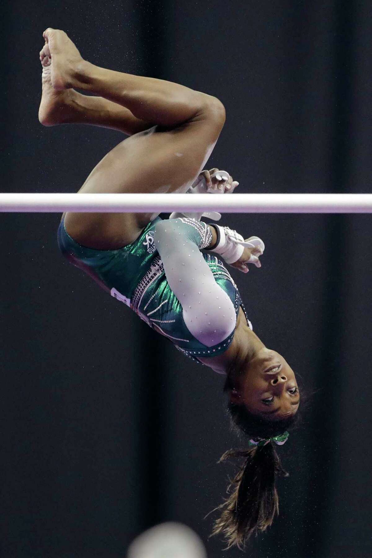 Simone Biles competes on the uneven bars during the senior women's competition at the U.S. Gymnastics Championships, Friday, Aug. 9, 2019, in Kansas City, Mo. (AP Photo/Charlie Riedel)