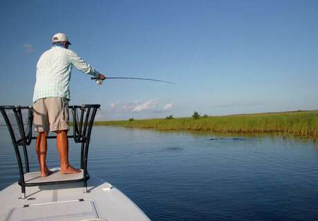 Angler Troy Utz casts a shrimp-imitation fly to a pod of redfish rooting for a meal of crustaceans or small finfish that thrive in the shoal grass-carpeted shallows of an inches-deep flat along Texas' middle coast.