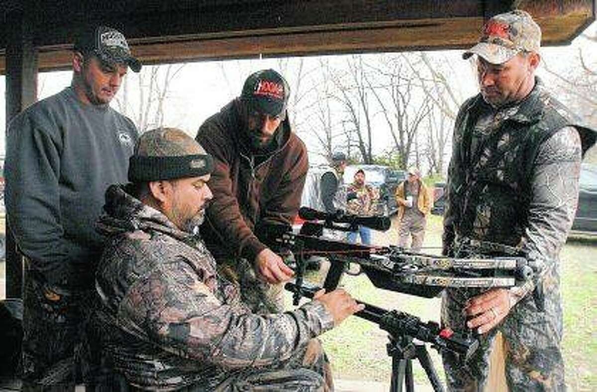 Josue Cordova of Naperville receives help setting up his crossbow at the HOOAH Deer Hunt for Heroes program at Funks Grove. The HOOAH Deer Hunt for Heroes program works to provide wounded veterans with opportunities they may have experienced in the military but are now applicable to civilian life.