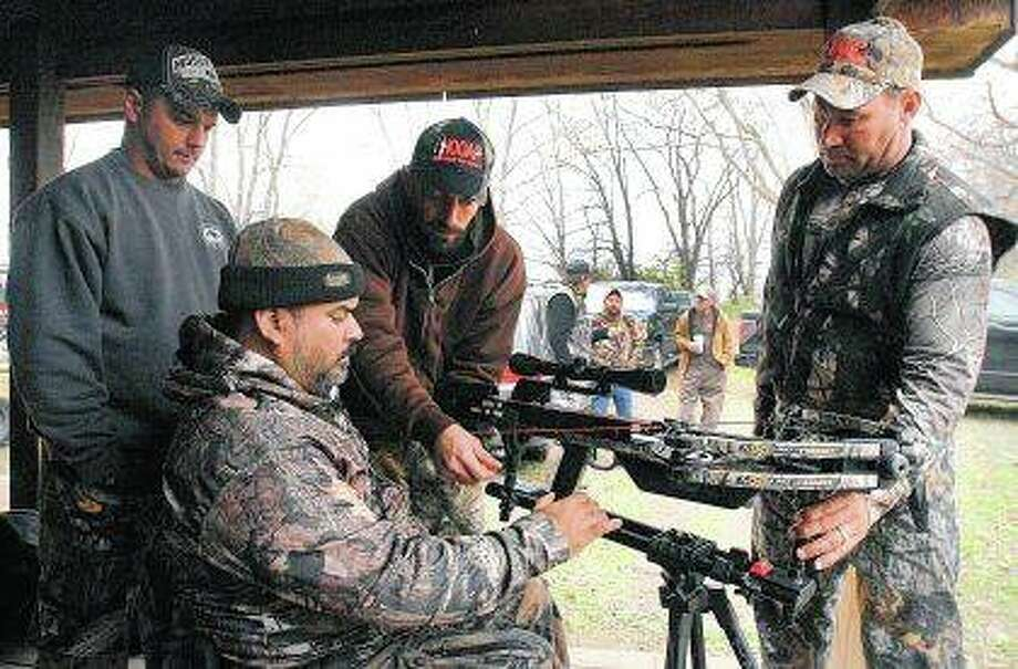 Josue Cordova of Naperville receives help setting up his crossbow at the HOOAH Deer Hunt for Heroes program at Funks Grove. The HOOAH Deer Hunt for Heroes program works to provide wounded veterans with opportunities they may have experienced in the military but are now applicable to civilian life. Photo: David Proeber | The Pantagraph (AP)