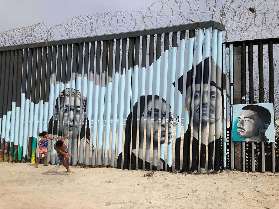 Children play in front of a new mural on the Mexican side of a border wall in Tijuana, Mexico Friday, Aug. 9, 2019. The mural shows faces of people deported from the U.S. with barcodes that activate first-person narratives on visitors' phones. Lizbeth De La Cruz Santana conceived the interactive mural in Tijuana as part of doctoral dissertation at the University of California, Davis. (AP Photo/Elliot Spagat) Photo: Elliot Spagat, Associated Press