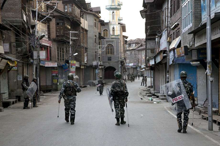 In this Friday, Aug. 9, 2019, photo, Indian Paramilitary soldiers patrol during curfew in Srinagar, Indian controlled Kashmir. Authorities enforcing a strict curfew in Indian-administered Kashmir will bring in trucks of essential supplies for an Islamic festival next week, as the divided Himalayan region remained in a lockdown following India's decision to strip it of its constitutional autonomy. The indefinite 24-hour curfew was briefly eased on Friday for weekly Muslim prayers in some parts of Srinagar, the region's main city, but thousands of residents are still forced to stay indoors with shops and most health clinics closed. All communications and the internet remain cut off. (AP Photo/ Dar Yasin) Photo: Dar Yasin / Associated Press