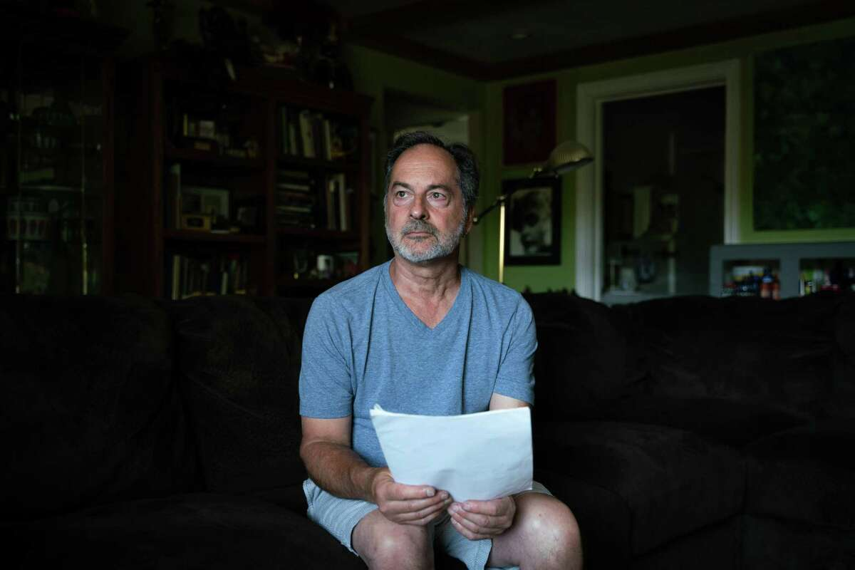 """Joey Piscitelli, 64, poses for a portrait holding court documents at his home in Martinez, Calif., on Wednesday, July 31, 2019. Piscitelli was sexually abused at the Boys Club in Richmond when he was 13-years-old. Then he was abused by a priest who was also the vice principal of his high school in Berkeley. Piscitelli said it took him 30 years to speak publicly about his abuse and that he knows some victims """"who never will."""""""