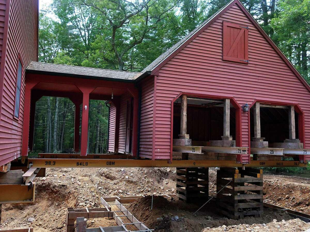 """In this July 1, 2019 photo, Peter Brenn's home in Willington, Conn., sits elevated so the concrete foundation can be replace. The foundation had been deteriorating due to the presence of an iron sulfide known as pyrrhotite, often described as """"a slow-moving disaster,"""" which causes concrete to crack and break gradually as it becomes exposed to water and oxygen. After worrying for years about the foundations crumbling beneath their houses, hundreds of suburban homeowners in a large swath of eastern Connecticut are getting help from the state to salvage their properties that had been doomed by bad batches of concrete."""