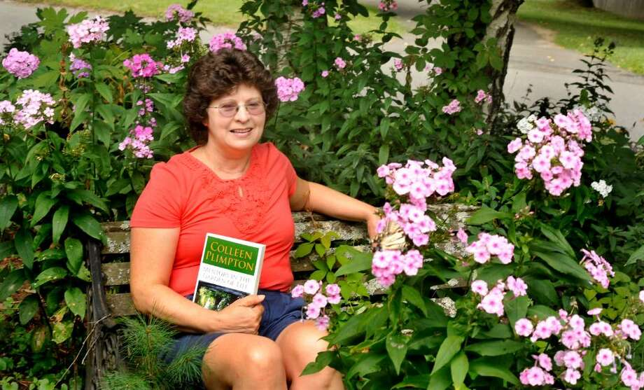 """Colleen Plimpton holds her book, """"Mentors in the Garden of Life,"""" in the front garden of her Bethel home, Tuesday, August 3, 2010. Photo: Michael Duffy / The News-Times"""