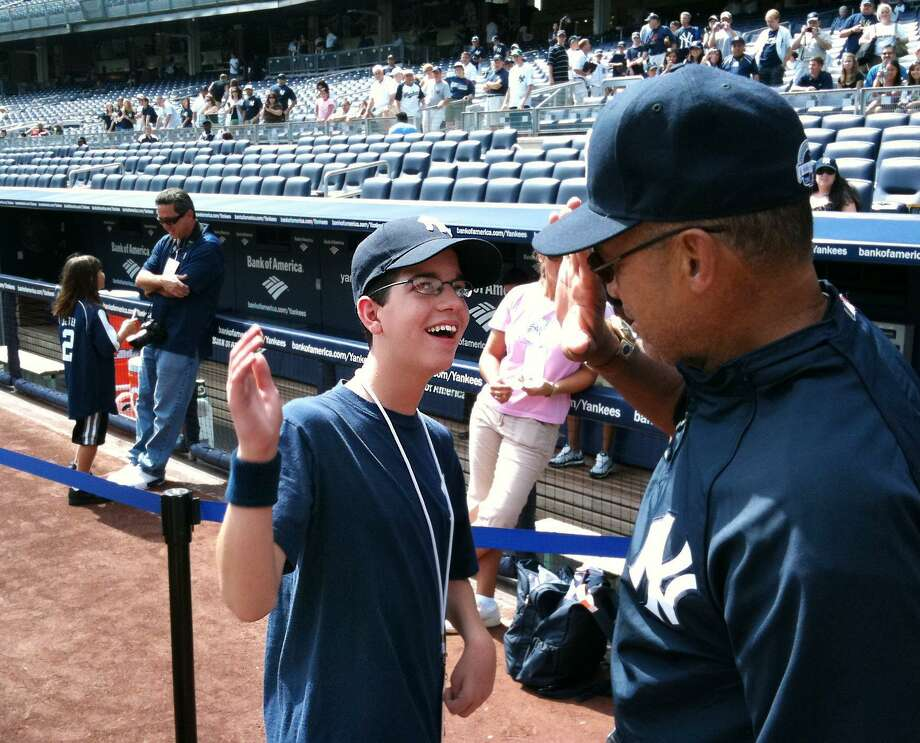 Justin Nemchek of Stamford, left, slaps hands with baseball legend, Mr. October, Reggie Jackson, right, at Yankee Stadium prior to game against Detroit. Nemchek a 14-year-old Stamford boy will undergo a serious surgery at Stamford Hospital aimed to eliminate or reduce some of his 40 daily seizures and remove a life-threatening clump of blood vessels in his brain. Photo: Dave Ruden / ST