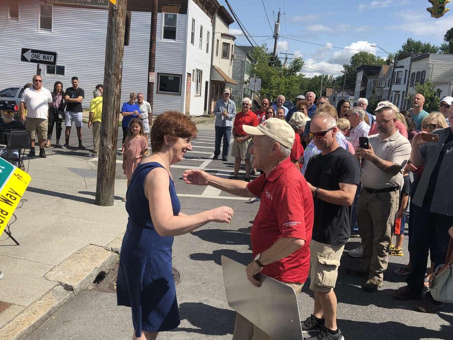 Albany Mayor Kathy Sheehan embraces John Aidala during a street renaming honoring his family. Photo: Chris Bragg