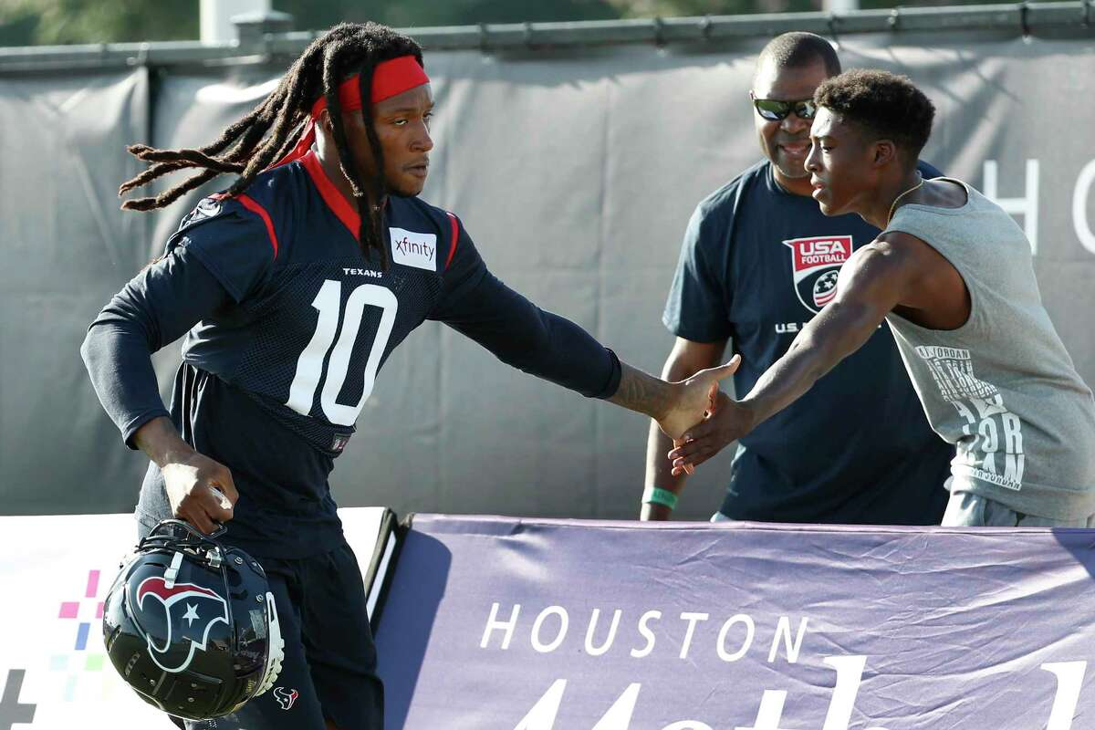 Houston Texans wide receiver DeAndre Hopkins (10) slaps hands with a fan as he runs to practice during training camp at the Methodist Training Center on Aug. 10, 2019, in Houston.