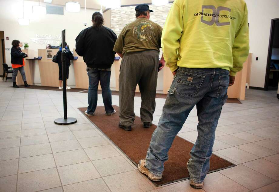 FILE - In this Nov. 16, 2018, file photo credit union members stand in line at Blackhawk Community Credit Union on East Milwaukee Street in Janesville, Wis. Credit unions, with their great savings and loan rates and excellent service, offer an alternative to traditional banks. (The Janesville Gazette via AP) / The Janesville Gazette