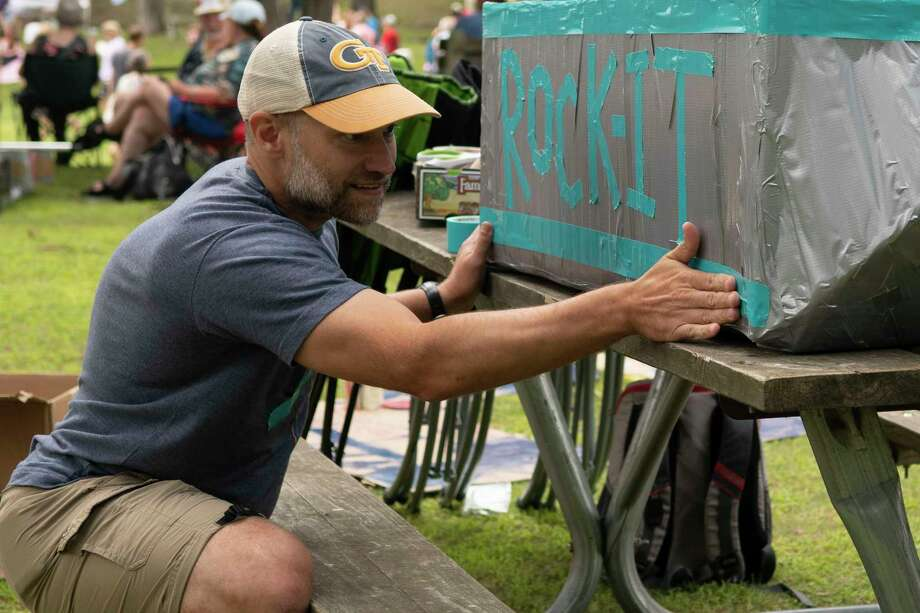 Rick Good of Saratoga lays a piece of duct tape on his sons' cardboard boat the 15th Annual Cardboard Boat Race at Fort Hardy Park on Saturday in Schuylerville. This year's race marks his sons' 3rd annual race. (Jenn March, Special to the Times Union) Photo: Jenn March / © Jenn March 2019 © Albany Times Union 2019