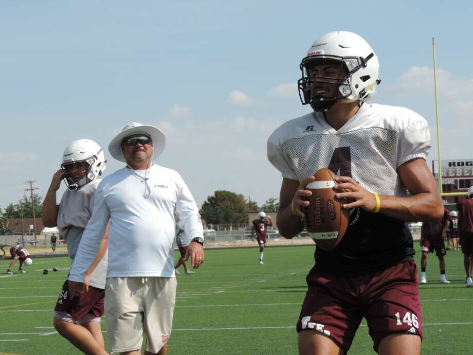 Lee quarterback Mikey Serrano, right, gets ready to throw the ball during a passing drill, while head coach Clint Hartman, left, watches on Aug. 9 at the Lee turf field. Photo: Christopher Hadorn