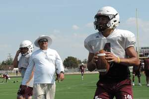 Lee quarterback Mikey Serrano, right, gets ready to throw the ball during a passing drill, while head coach Clint Hartman, left, watches on Aug. 9 at the Lee turf field.