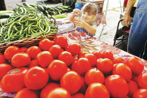 Marley Beilsmith, 4, of Jerseyville, plays with a green bean as she helps her grandfather, Bob Sancamper, at his produce stand in the Alton farmer's market on the parking lot at the foot of Henry Street in Alton. Despite a rainy start to this year's season, vendors at local farmers' markets say they are having a good year.