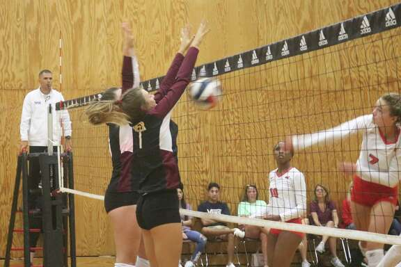 The block attempt by two Deer Park players wasn't needed as this kill attempt by The Woodlands flies into the net.