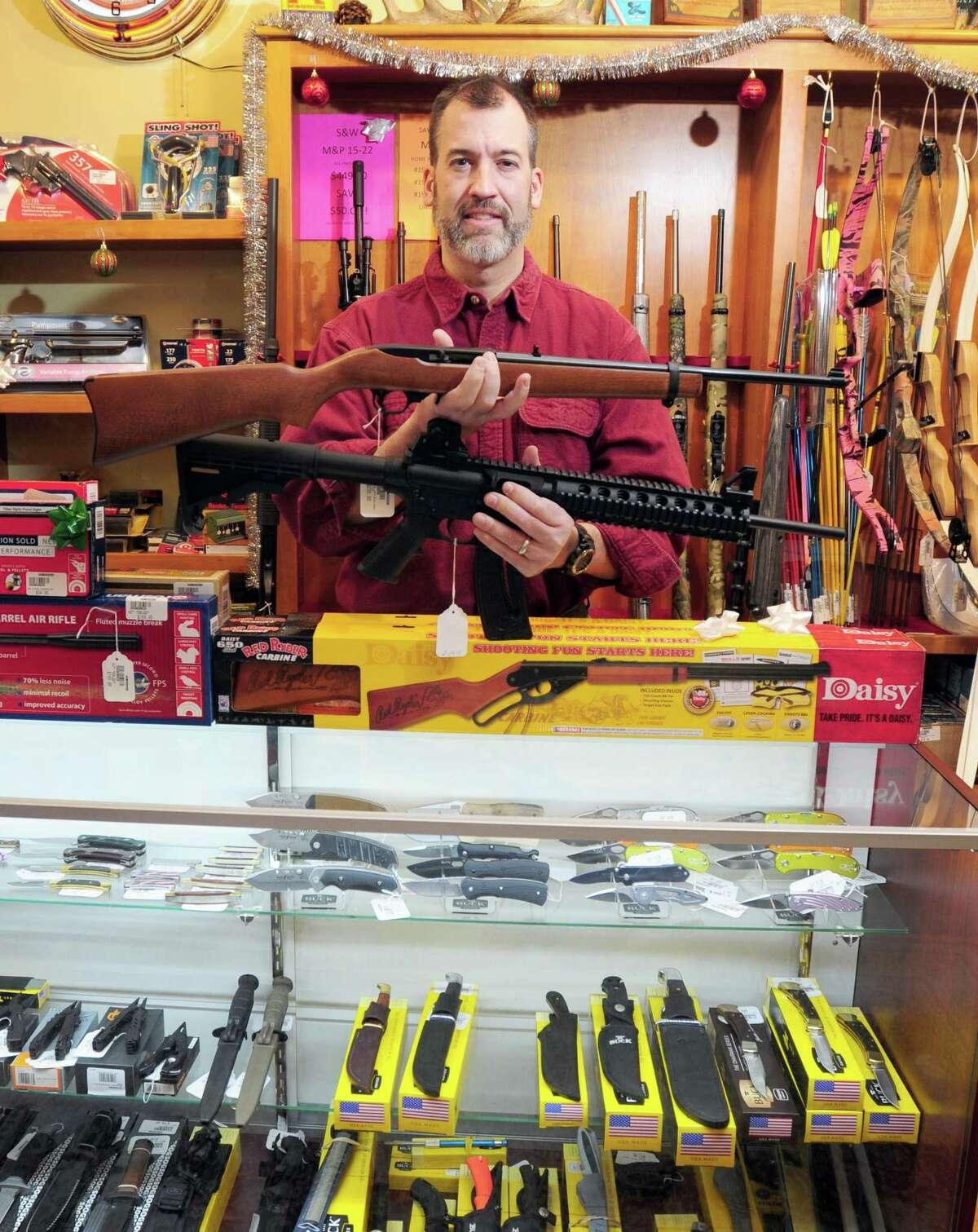 Mike Higgins, co-owner of TGS Outdoors in Branford, holds a Ruger 10/22 semi-automatic rifle, above, and a Smith & Wesson M&P 15/22 semi-automatic rifle, below, both chambered in .22 Long Rifle in 2013.