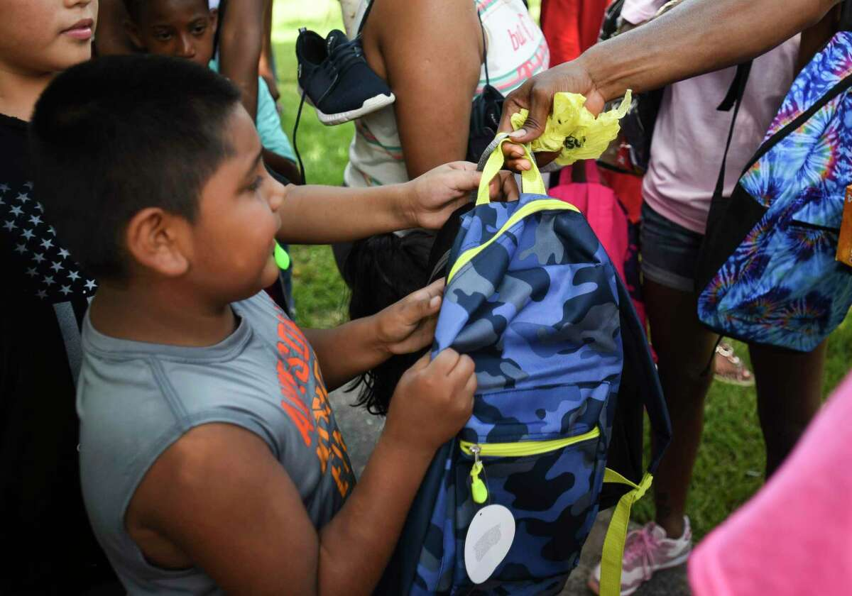 Families get handed backpacks during Kendrick Perkins' giveaway of 1,000 backpacks loaded with school supplies at Roberts Park Saturday afternoon. Photo taken on Saturday, 08/10/19. Ryan Welch/The Enterprise