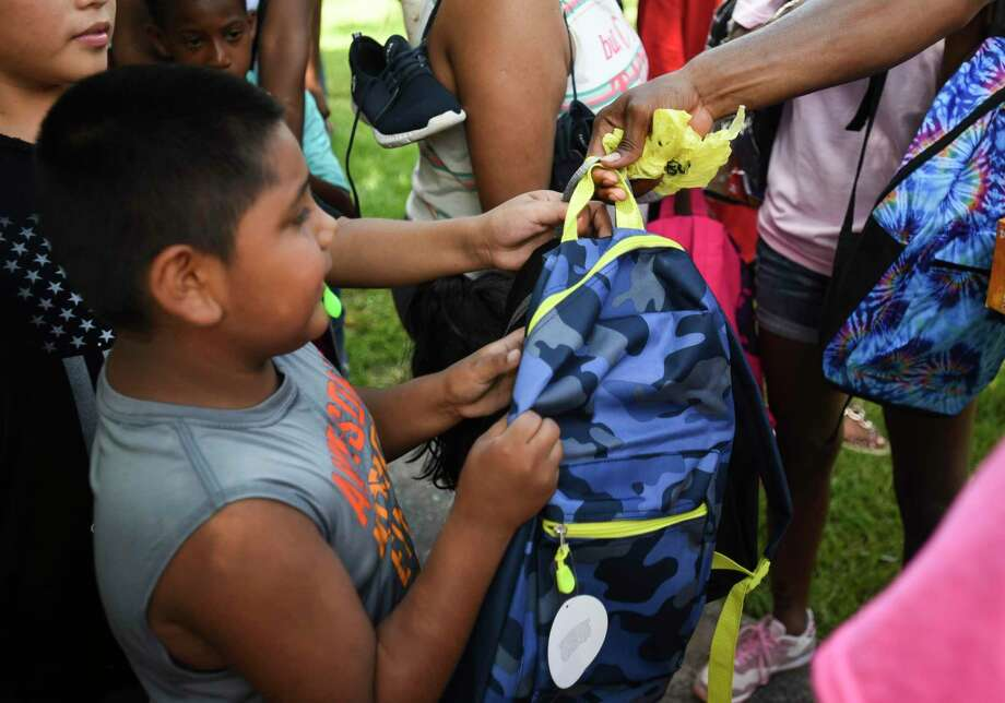 Families get handed backpacks during Kendrick Perkins' giveaway of 1,000 backpacks loaded with school supplies at Roberts Park Saturday afternoon.