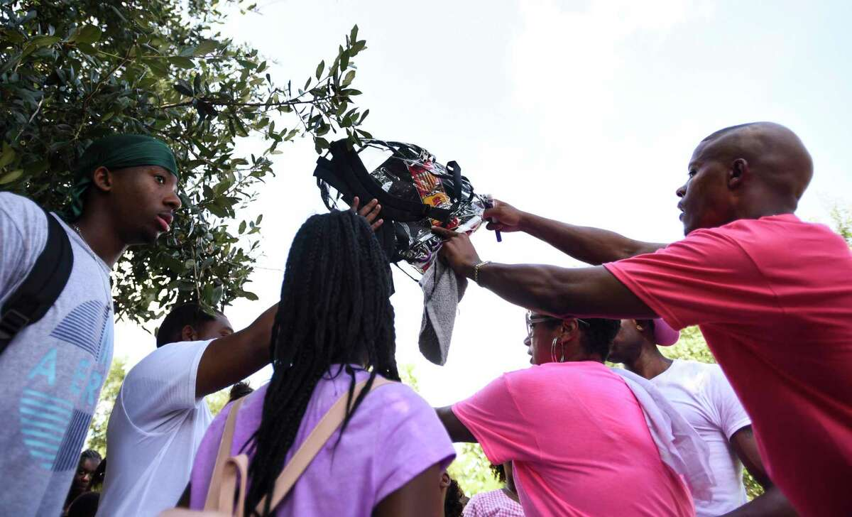 Jerrial Citizen gives a family a backpack during Kendrick Perkins' giveaway of 1,000 backpacks loaded with school supplies at Roberts Park Saturday afternoon. Photo taken on Saturday, 08/10/19. Ryan Welch/The Enterprise