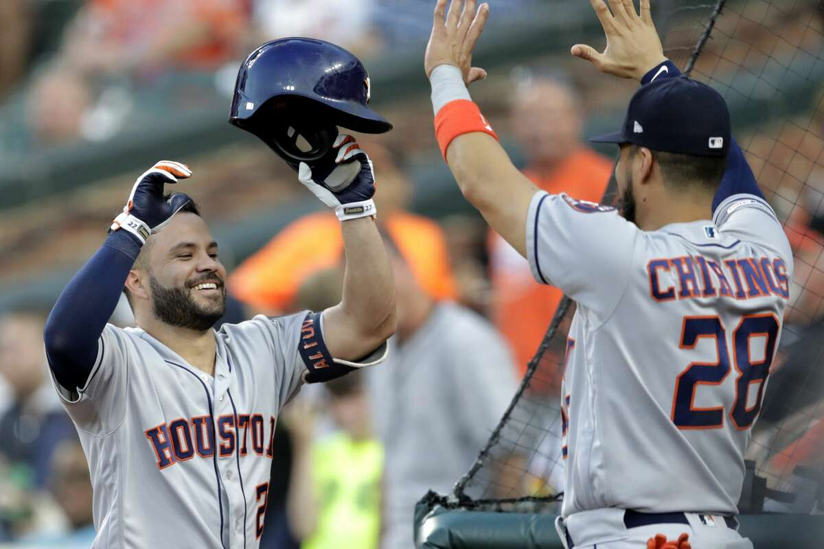 Houston Astros' Jose Altuve, left, is greeted near the dugout by Robinson Chirinos after hitting a two-run home run off Baltimore Orioles starting pitcher Aaron Brooks during the second inning of a baseball game Saturday, Aug. 10, 2019, in Baltimore. (AP Photo/Julio Cortez)