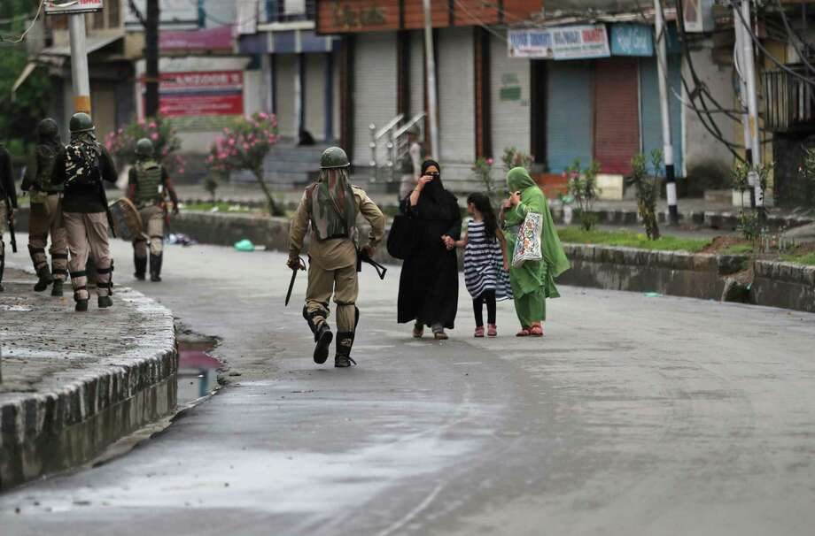 Kashmiris walks past Indian paramilitary soldiers patrolling a street in Srinagar, Indian controlled Kashmir, Saturday, Aug. 10, 2019. Authorities enforcing a strict curfew in Indian-administered Kashmir will bring in trucks of essential supplies for an Islamic festival next week, as the divided Himalayan region remained in a lockdown following India's decision to strip it of its constitutional autonomy. The indefinite 24-hour curfew was briefly eased on Friday for weekly Muslim prayers in some parts of Srinagar, the region's main city, but thousands of residents are still forced to stay indoors with shops and most health clinics closed. All communications and the internet remain cut off. (AP Photo/Mukhtar Khan) Photo: Mukhtar Khan / Copyright 2019 The Associated Press. All rights reserved.