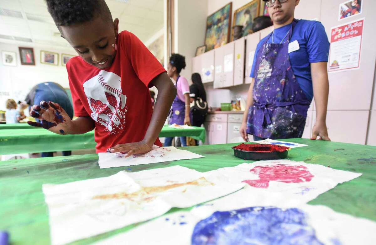 Jacovin Brown, 7, presses a sheet onto a ink cover fish during AMSET's Summer Family Arts Days event Saturday at the museum. Photo taken on Saturday, 8/10/19. Ryan Welch/The Enterprise