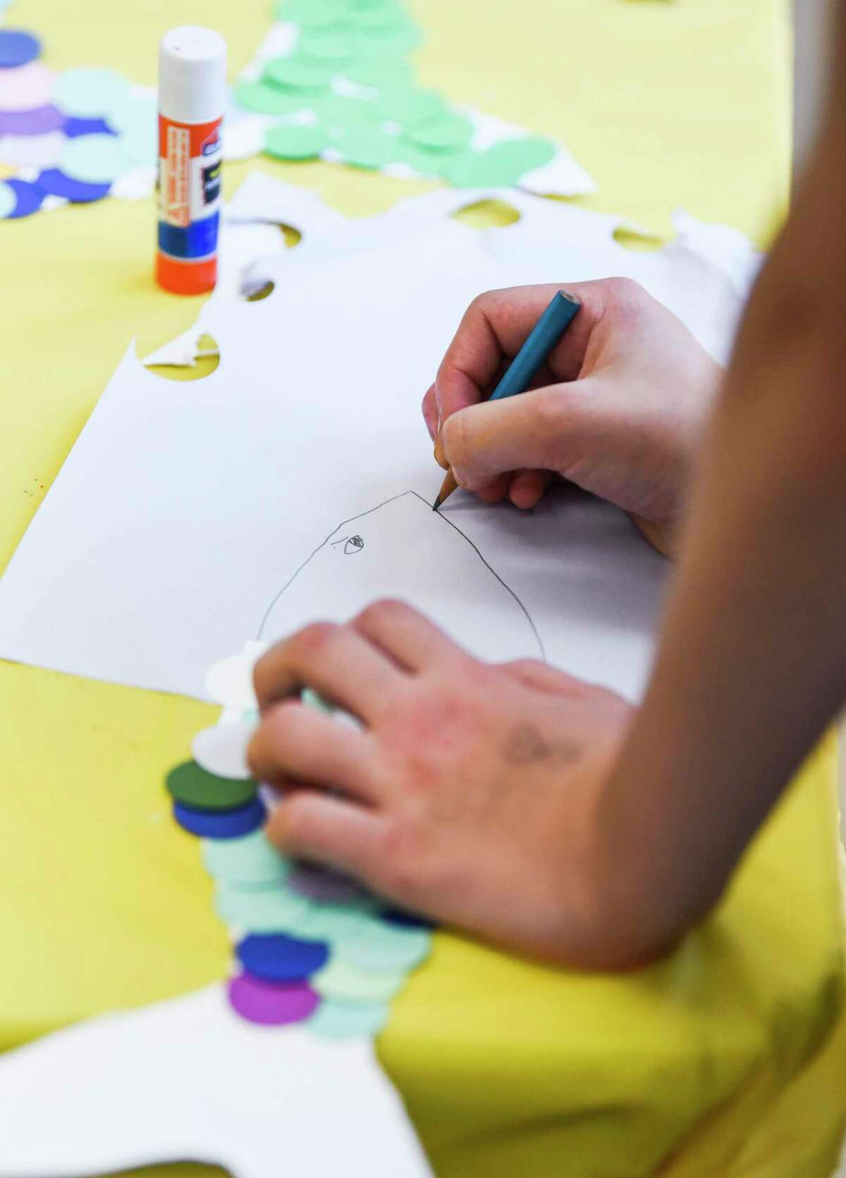 A child draws the outlines of a fish that she will cover in paper scales during AMSET's Summer Family Arts Days event Saturday at the museum. Photo taken on Saturday, 8/10/19. Ryan Welch/The Enterprise