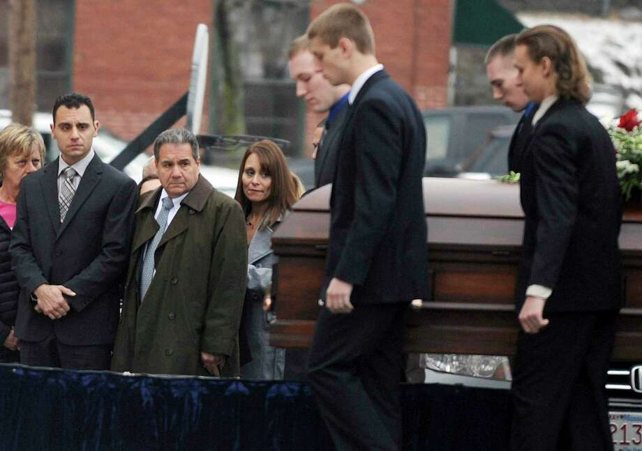In this Dec. 30, 2015 photo, Richard Dabate, left, watches the casket bearing his late wife Connie Dabate being carried during her funeral outside St. Bernard Roman Catholic Church in Vernon, Conn. While responding to a burglary alarm on Dec. 23, authorities found Connie Dabate, mother of two children, shot to death and her husband Richard Dabate injured inside their Ellington, Conn., home. No arrests have been made, leaving local residents concerned and speculating. Photo: Jim Michaud / Associated Press / Journal Inquirer