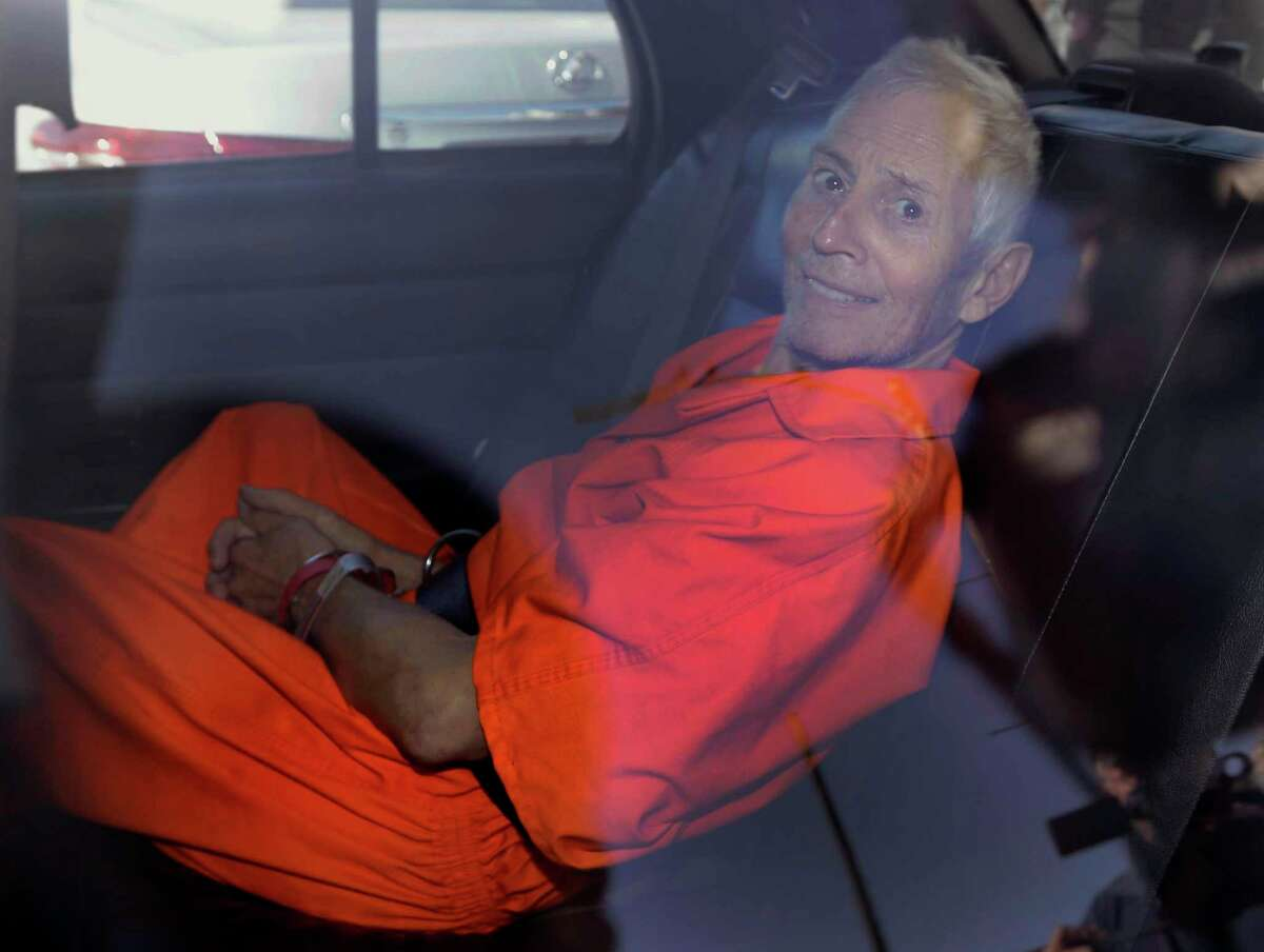 FILE - In this Tuesday, March 17, 2015, file photo, Robert Durst is transported from Orleans Parish Criminal District Court to the Orleans Parish Prison after his arraignment in New Orleans. The whispered words of Durst recorded in an unguarded moment in a bathroom could come back to haunt him - or help him - as he faces a murder charge. A possible move by prosecutors to introduce the incriminating material from a six-part documentary on his strange life and connection to three killings could back fire as interview footage did in the Michael Jackson molestation trial and the Robert Blake murder case.
