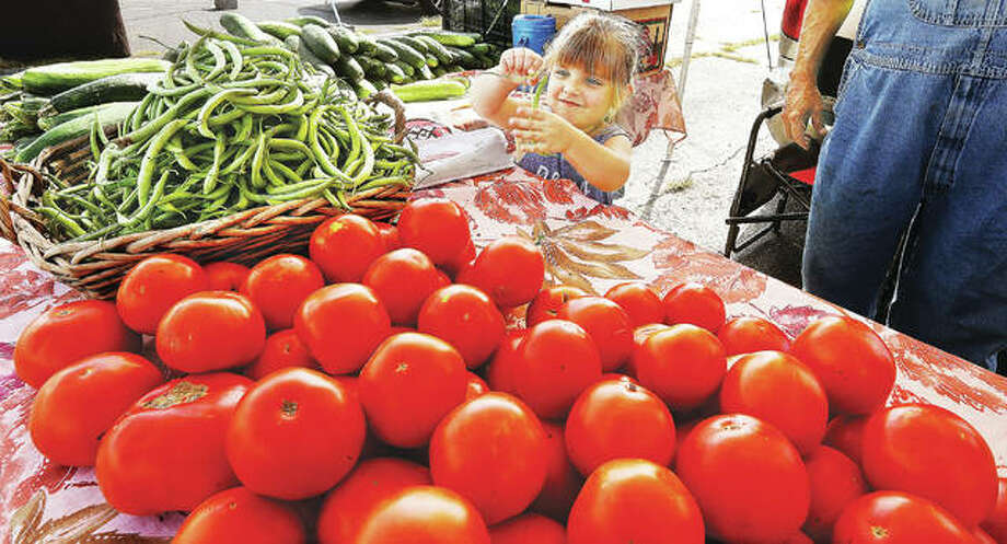 Marley Beilsmith, 4, of Jerseyville, plays with a green bean as she helps her grandfather, Bob Sancamper, at his produce stand in the Alton farmer's market on the parking lot at the foot of Henry Street in Alton. Despite a rainy start to this year's season, vendors at local farmers' markets say they are having a good year. Photo: John Badman| Hearst Illinois