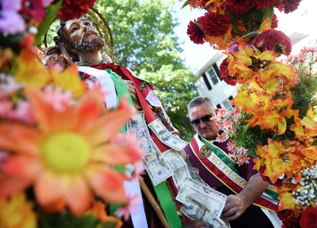Mario Montonarano pins money to the statue of St. Roch as the 110th annual St. Roch Church procession moves through the streets in the Chickahominy section of Greenwich, Conn. Sunday, Aug. 11, 2019. To close out the Feast, the church paid tribute to St. Roch with a procession featuring a statue of St. Roch and music from the Dixie Dandies. Onlookers crowded the streets and pinned money to ribbons on the statue as the procession made its way through town.