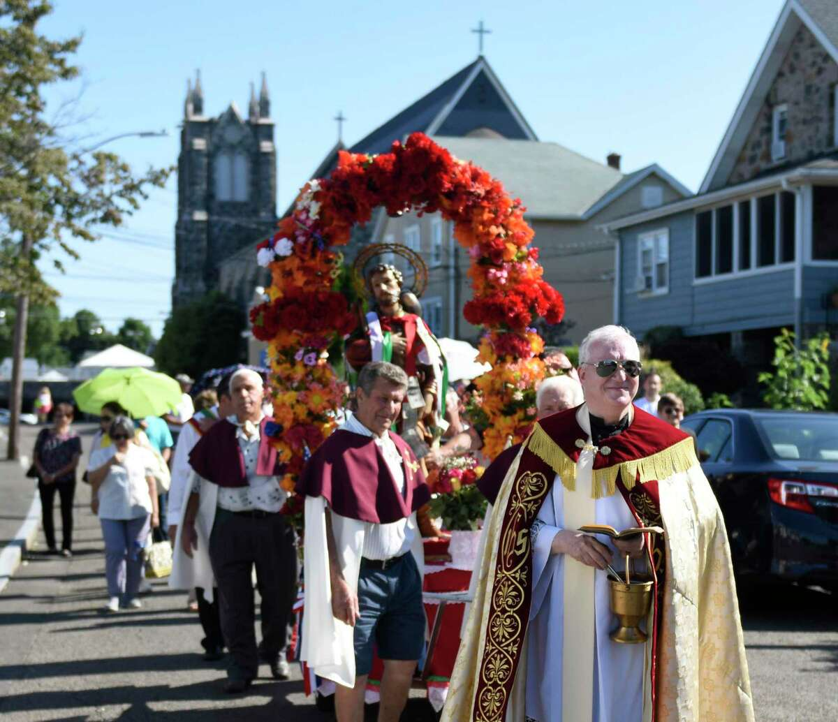 The Rev. Carl McIntosh leads the 110th annual St. Roch Church procession through the streets in the Chickahominy section of Greenwich, Conn. Sunday, Aug. 11, 2019. To close out the Feast, the church paid tribute to St. Roch with a procession featuring a statue of St. Roch and music from the Dixie Dandies. Onlookers crowded the streets and pinned money to ribbons on the statue as the procession made its way through town.