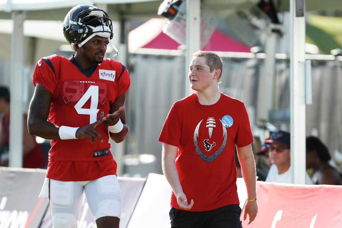 Houston Texans quarterback Deshaun Watson (4) walks onto the practice field with Ethan Hughes, who was a guest of the Texans through the Make-A-Wish Foundation, during training camp at the Methodist Training Center on Aug. 10, 2019, in Houston. After practice Hughes, who is battling leukemia, played catch with Watson and even caught a few touchdown passes.