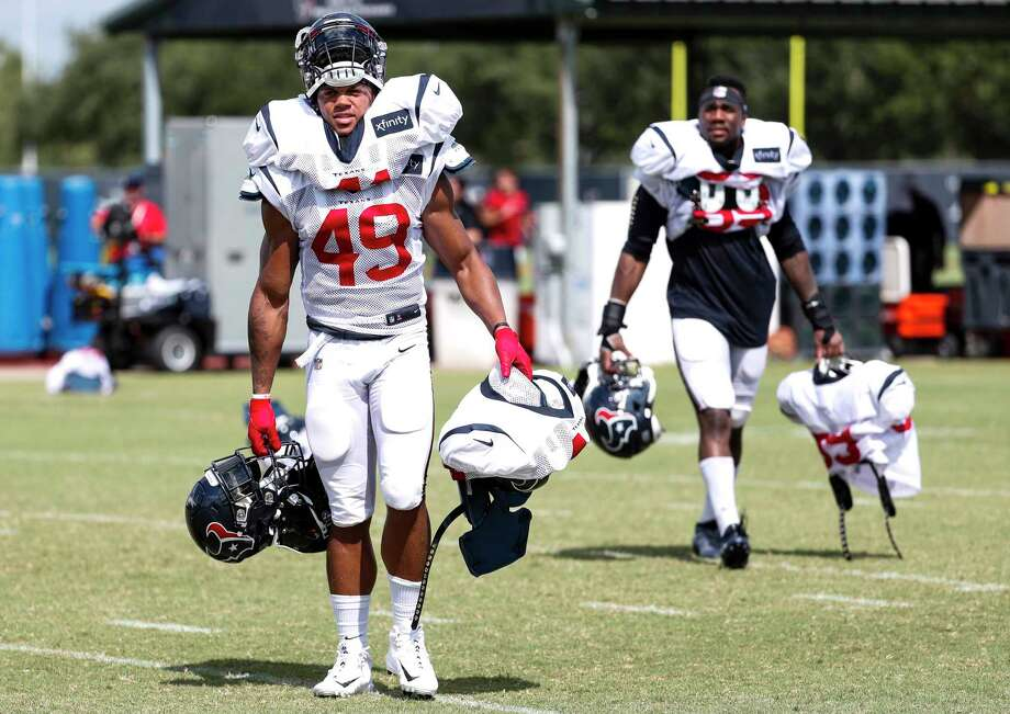 Houston Texans rookie linebackers Jamal Davis (49) and Jesse Aniebonam (69) carry off some of the veterans' pads and helmets at the end of practice during training camp at the Methodist Training Center on Aug. 10, 2019, in Houston. Photo: Brett Coomer, Staff Photographer / © 2019 Houston Chronicle
