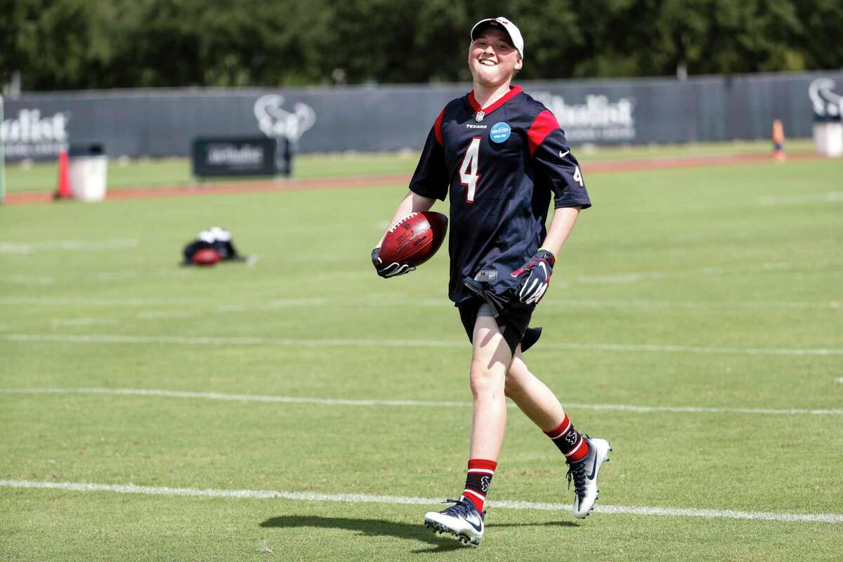 Ethan Hughes is all smiles after catching a touchdown pass from Houston Texans quarterback Deshaun Watson at the end of practice during training camp at the Methodist Training Center on Aug. 10, 2019, in Houston. Hughes, who is battling leukemia and was a guest of the Texans through the Make-A-Wish Foundation, played catch with Watson and also caught a couple touchdown passes from Watson.