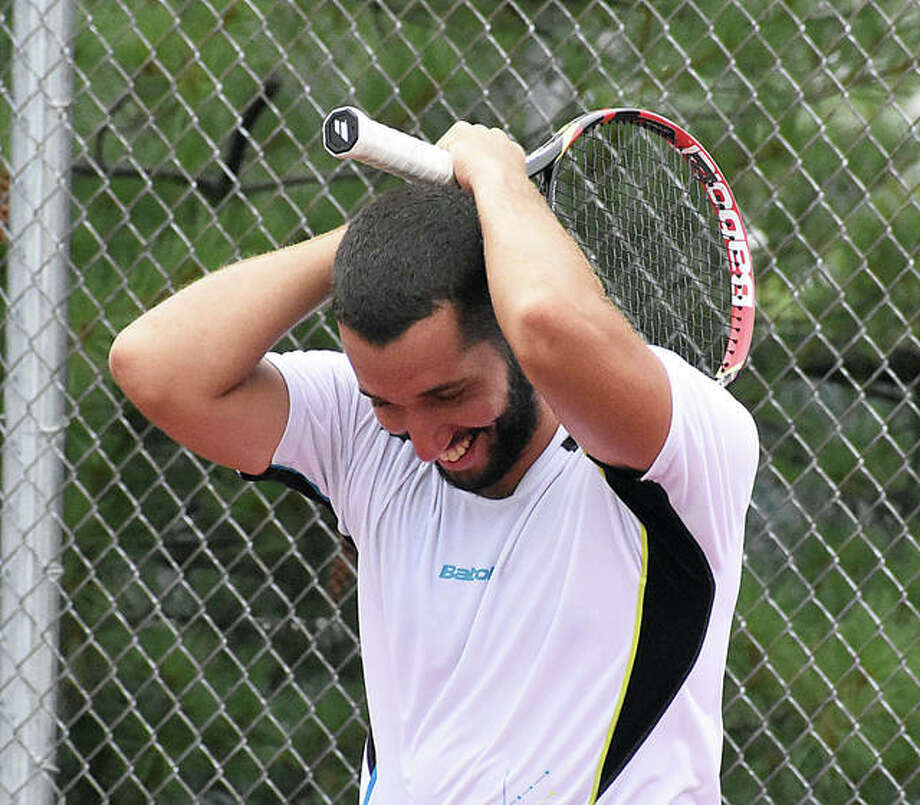 Petros Chrysochos smiles after watching his backhand shot bounce off the net and trickle in for match point to win the Edwardsville Futures tournament on Sunday at the EHS Tennis Center.
