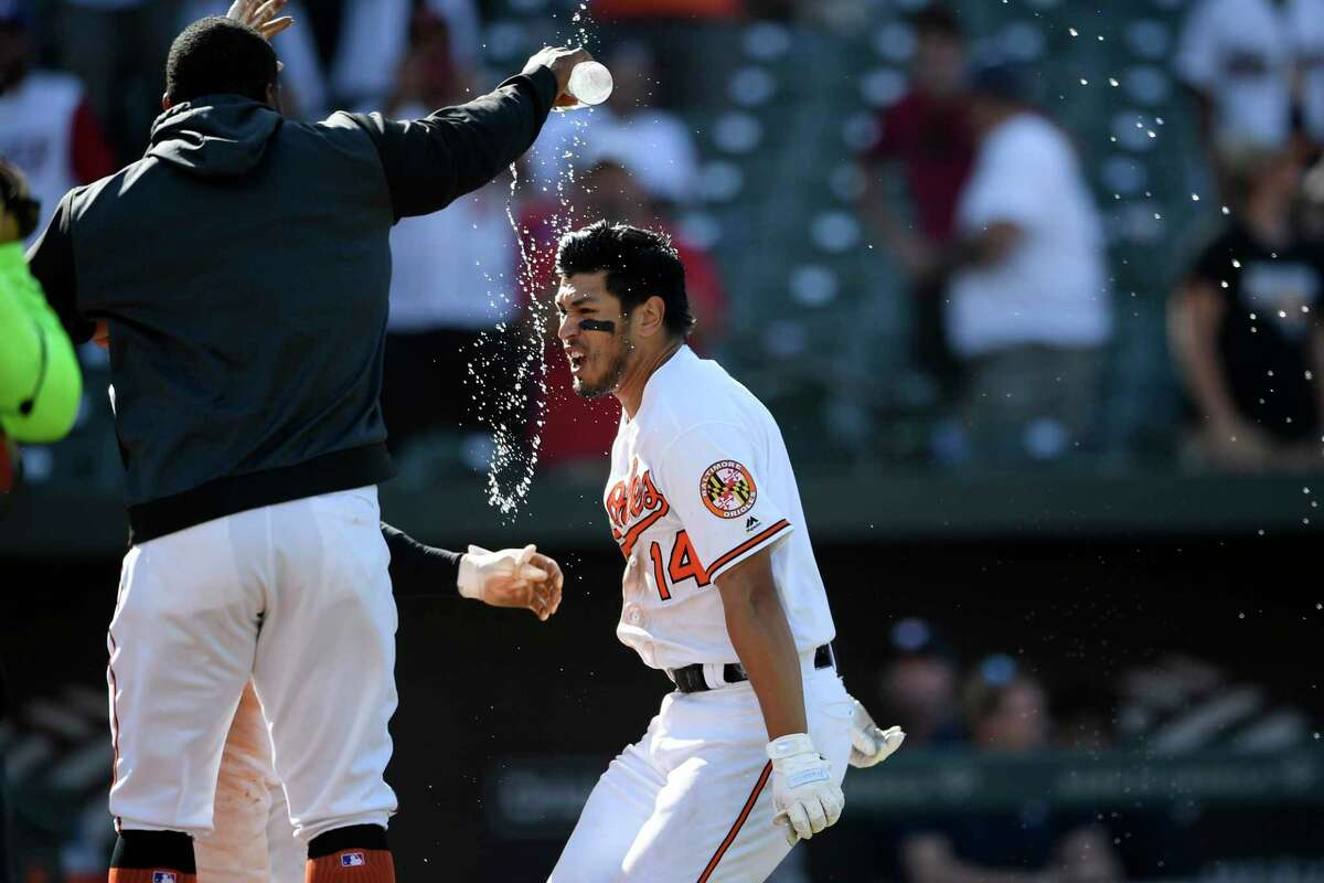 Baltimore Orioles' Rio Ruiz (14) gets water thrown at him as he approaches home plate after he hit a two-run walkoff home run in a baseball game against the Houston Astros, Sunday, Aug. 11, 2019, in Baltimore. The Orioles won 8-7. (AP Photo/Nick Wass)