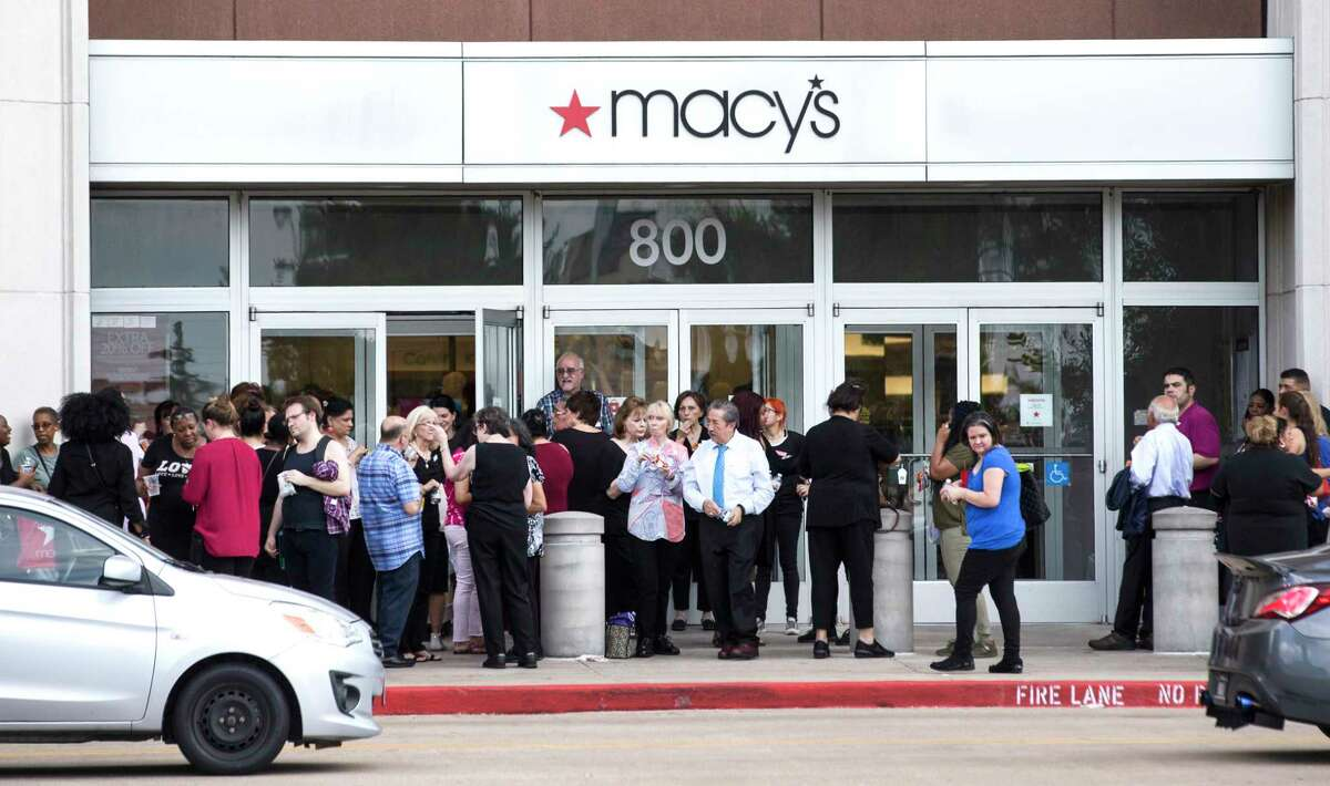 People stand outside Memorial City Mall where a disturbance forced an evacuation of the shopping center on Sunday, Aug. 11, 2019, in Houston.