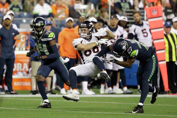 Seattle Seahawks defensive back Marquise Blair, right, hits Denver Broncos wide receiver Nick Williams, center, drawing a penalty flag for unnecessary roughness, as Seahawks defensive back Simeon Thomas, left, watches during the second half of an NFL football preseason game Thursday, Aug. 8, 2019, in Seattle.