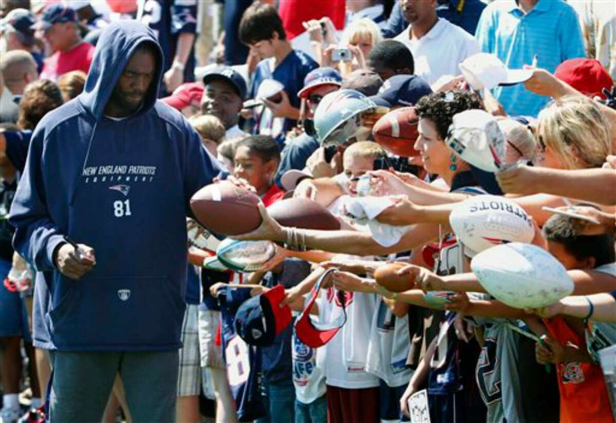 New England Patriots' Randy Moss signs autographs during NFL football training camp, Saturday, July 31, 2010, in Foxborough, Mass. (AP Photo/Michael Dwyer)