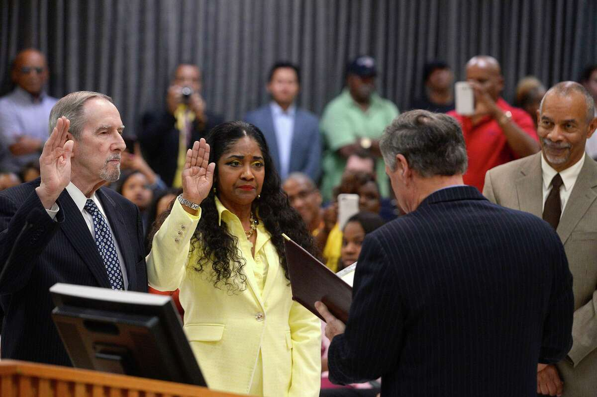 Nathan Cross and Denise Wallace-Spooner take the oath of office from Judge John Stevens as they're sworn in as new Beaumont ISD trustees during the board meeting last year. BISD has been under a state-appointed board of managers since 2014, though it has started transitioning elected officials onto the board.