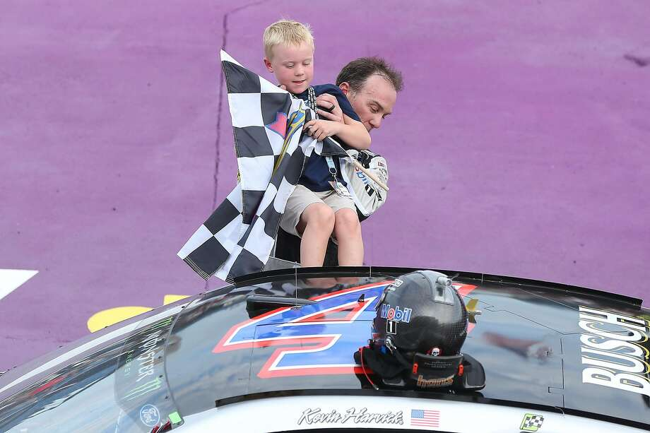 Kevin Harvick helps his son Keelan into the car with the checkered flag after winning Sunday. Photo: Matt Sullivan / Getty Images